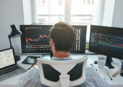 Trading stocks online. Back view of young businessman or trader working with graph and charts on computers at his modern office